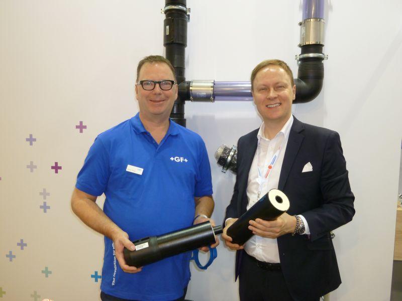 Markus Kerger (li.) und Attila Albert (re.) zeigen die Vorteile des Rohrleitungssystems »Cool-Fit« gegenüber isolierten Stahlrohren. Bild: Kuhn